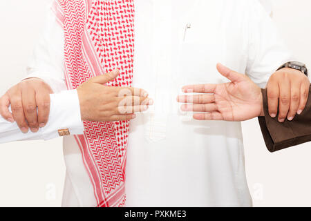 Saudi man holds two hands persons to reconciliation agreement as shake hands concept - Stock Image