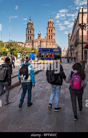 Young students walk through the Plaza De Armas toward the Cathedral of San Luis Potosi in the historic center of the state capital of San Luis Potosi, Mexico. Also known as the San Luis Potosi Metropolitan Cathedral, it is consider the most important monument in the state and the first Baroque style building constructed in 1670 on the site of a parish church first built in 1593. - Stock Image