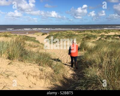 A young woman admires a deserted beach from the sand dunes. - Stock Image