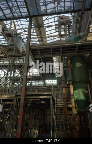 Industrial background, big old abandoned factory hall with stairs and day light - Stock Image