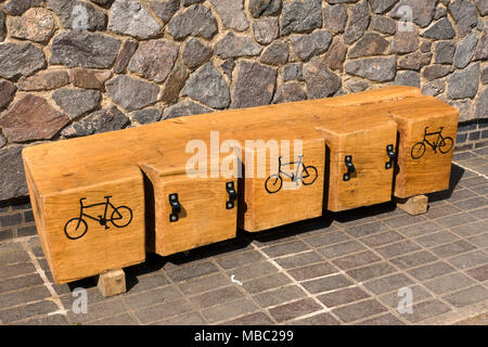 Large wooden log cut with slots to make a cycle rack - Stock Image