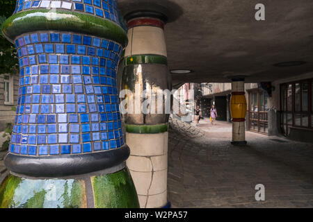 Tiled columns at Hundertwasserhaus, by architect Friedensreich Hundertwasser (a pseudonym), a local tourist attraction, Vienna, Austria. - Stock Image