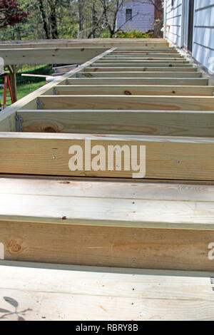 Unfinished construction frame of a house's new exterior wood deck being built in Springtime - Stock Image