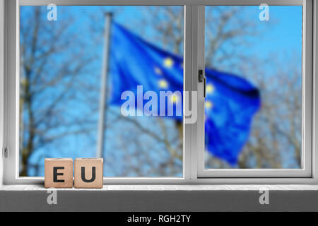 EU sign in a window with the European union flag outside waving in the wind - Stock Image