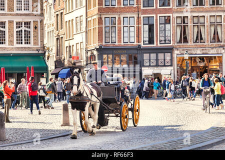 25 September 2018: Bruges, Belgium - Horse and carriage ride in beautiful and historic central Bruges, with tourists taking photos on a sunny autumn d - Stock Image