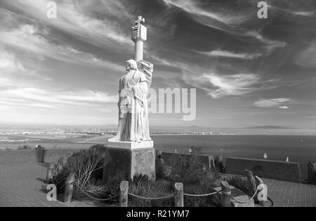 Black and White Photo of Cabrillo National Monument Statue at Point Loma and San Diego Bay Seascape in the Background - Stock Image