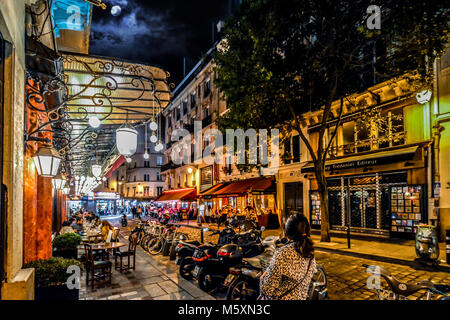 A woman tourist walks along a lively street in the Latin Quarter of Paris France with colorful cafes, shops and - Stock Image