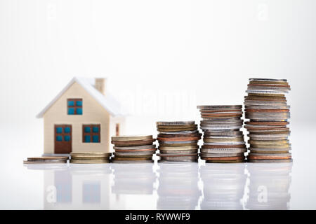 Increasing Coins Arranged In Front Of House Model Over White Desk - Stock Image
