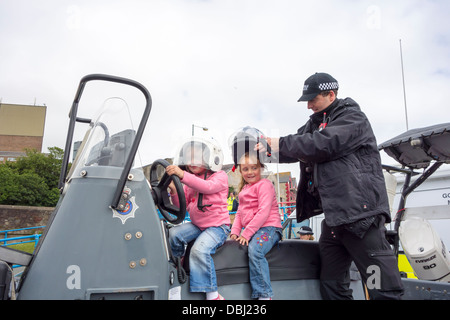 Two young girls sitting on a police boat at the Pembrokeshire Fish Week event in Milford Haven - Stock Image