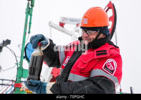 Kogalym, Russia. 21st Mar, 2019. KOGALYM, RUSSIA - MARCH 21, 2019: A worker shows oil samples at the Yuzhno-Yagunskoye oil field developed by Kogalymneftegaz, a subsidiary of the Lukoil-West Siberia oil and gas company. Vyacheslav Prokofyev/TASS Credit: ITAR-TASS News Agency/Alamy Live News - Stock Image