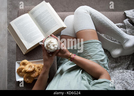 pretty girl reading book at home on couch with hot chocolate milk and cookies - Stock Image