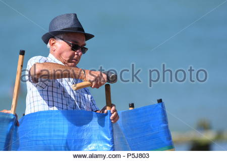 Littlehampton, UK. Wednesday 27th June 2018. People arrive at the seaside and put up a windbreak on another very warm and sunny morning in Littlehampton, on the South Coast. Credit: Geoff Smith / Alamy Live News. - Stock Image