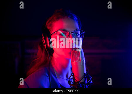 A young woman in glasses singing by the microphone in red and blue neon lighting - Stock Image