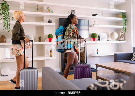 Young women friends with suitcases arriving at house rental - Stock Image