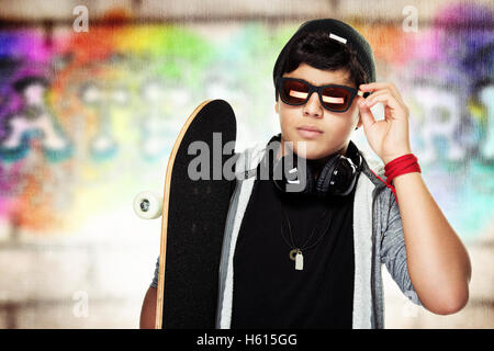 Portrait of a handsome skateboarder wearing sunglasses and stylish hat, active stylish teen - Stock Image