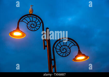 Old fashioned iron street lighting at Lyme Regis - Stock Image