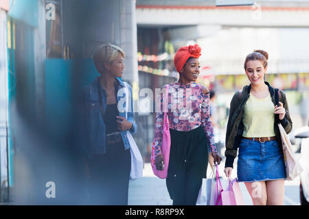 Young women friends walking with shopping bags on urban sidewalk - Stock Image