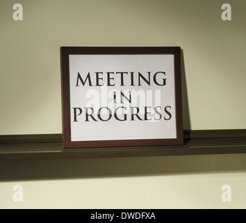 framed meeting in progress sign on shelf - Stock Image
