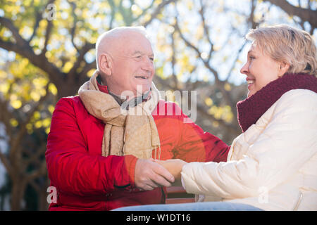 Aged husband and wife sitting together and talking on bench in park - Stock Image