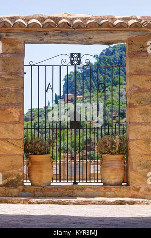 Gateway of the Iglesia de San Juan Bautista church in Mallorca, Spain provides a view of tree-covered hills in Deia. - Stock Image
