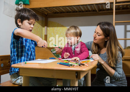 Brothers enjoying with colored pencils while mother is assisting them, Munich, Germany - Stock Image