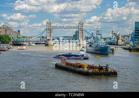 A busy scene on The River Thames in front Tower Bridge with a passenger ferry and tug pushing a pontoon passing each other in close proximity. - Stock Image