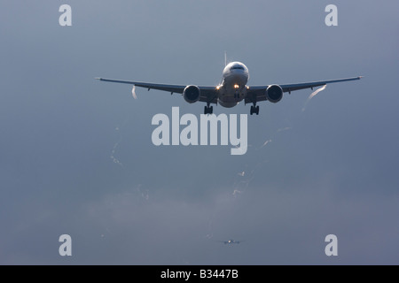 Commercial aeroplane on approach with visible wingtip vortices - Stock Image
