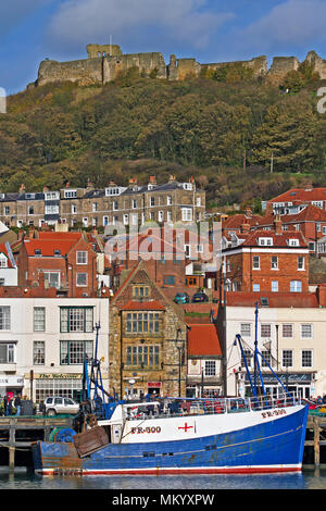 Scarborough Castle and ramparts sit high above a fishing boat moored in the town's harbour below. - Stock Image