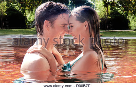 Young couple embracing in orange swimming pool - Stock Image