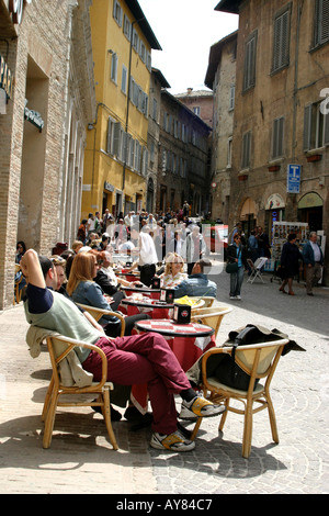 people enjoying sunshine at a street cafe in Urbino Le Marche, the Marches, Italy - Stock Image