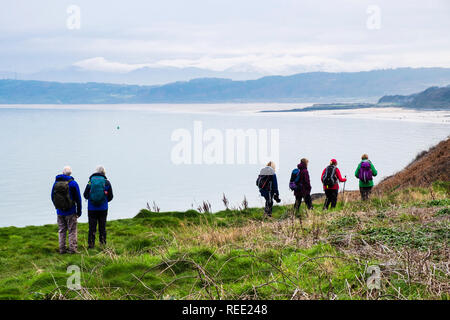 People hikers hiking on island of Anglesey Coastal Path with a view across calm sea to Red Wharf Bay. Benllech, Isle of Anglesey, Wales, UK, Britain - Stock Image