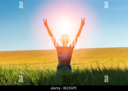 Back view of a woman at sunrise with her arms raised in joy and freedom standing in a field of wheat - Stock Image