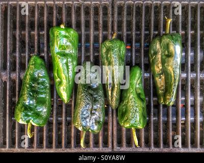 Poblano peppers roasting in preparation for Mexican meal - Stock Image