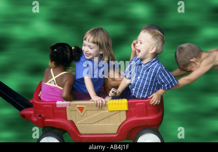 Children riding in a red wagon - Stock Image