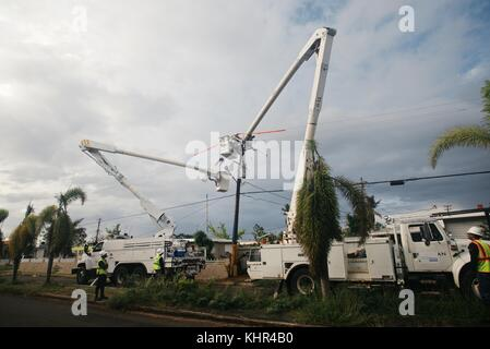 Utility workers repair a damaged electrical transformer to restore power during relief efforts in the aftermath - Stock Image