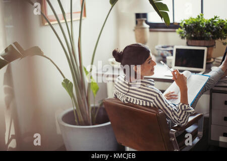 Businesswoman reading paperwork with feet up on desk - Stock Image