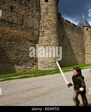 boy with sword playing in front of walled village of Carcassonne France - Stock Image