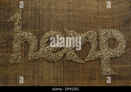 The word Hemp written artistically in hemp seeds on a wooden chopping board, with a heart shape integrated into the word. - Stock Image
