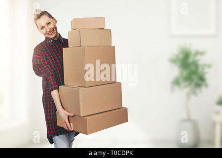 happy woman standing in new house with boxes in hands - Stock Image