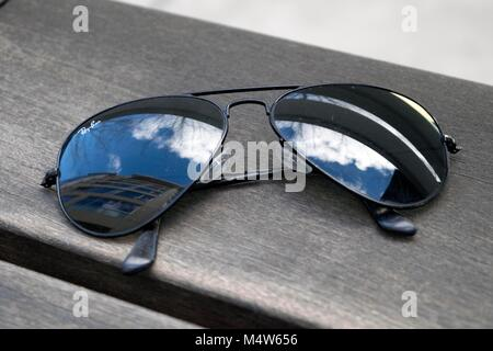 A pair of sunglasses rests on a table at a cafe. - Stock Image