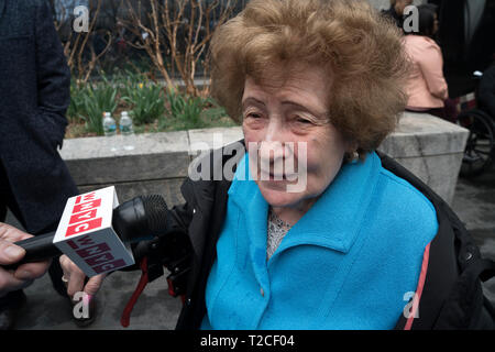 """New York, USA. 31st Mar, 2019. Ray Kaner, 92, who was transported from Lodz, Poland to Auschwitz in August 1944, described her experiences on the plaza in front of the Museum of Jewish Heritage in Battery Park City, Manhattan, New York, where a German National Railroad freight car had just been installed. It is part of the museum's upcoming exhibition, """"Auschwitz. Not long ago. Not far away."""" This freight car, which would have been packed with 80 to 100 people, was one of many that the Nazis used to transport people — most of them, Jews — to Auschwitz to be killed. Credit: Terese Loeb Kreuzer - Stock Image"""