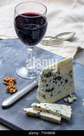 Piece of French blue cheese Roquefort, made from sheep milk in caves of Roquefort-sur-Soulzon and glas with red wine - Stock Image