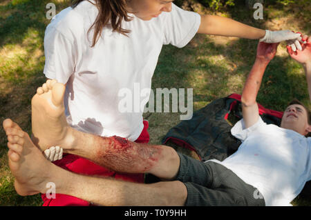 First aid treatment of leg-injured patient by young female. - Stock Image