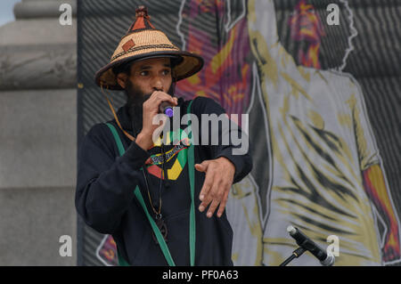 London, UK. 18th August 2018. Musician and Notting Hill community leader Niles Hailstones introduces the annual National Memorial event in Trafalgar Square to remember and honour the victims of the African Holocaust/Transatlantic Slave Trade and promote International Slavery Remembrance Day, 23rd August. The event called for Africans to celebrate their identity and to remember their ancestors, and began with libations remembering many black heroes. e Credit: Peter Marshall/Alamy Live News - Stock Image