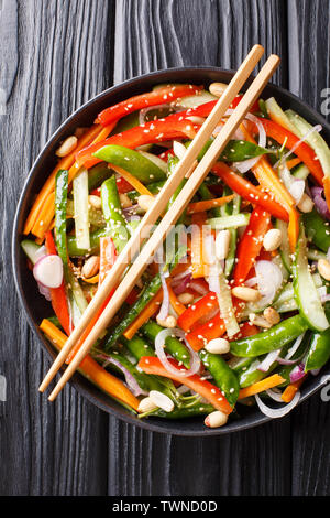 Chinese fresh vegetable salad with sesame and peanuts close-up on a plate on the table. Vertical top view from above - Stock Image