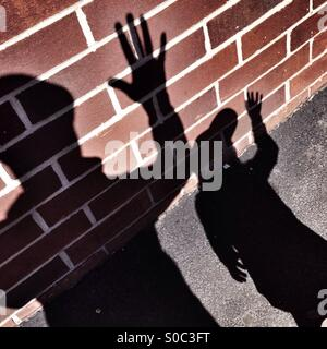 Father and daughter silhouettes on brick wall - Stock Image