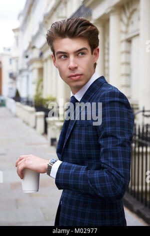 Young man in blue check suit in street with coffee, close up - Stock Image