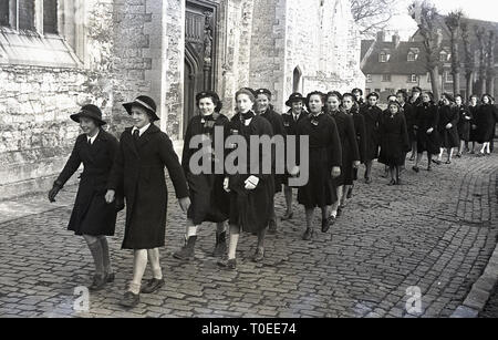 1948, a group of boarding school children walking on a cobbled path inside church grounds on the way to a Sunday service, England, UK. - Stock Image