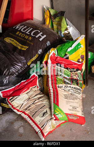 Bags of mulch, fertilizer and weed killer for lawns piled in a garage. Kansas, USA. - Stock Image