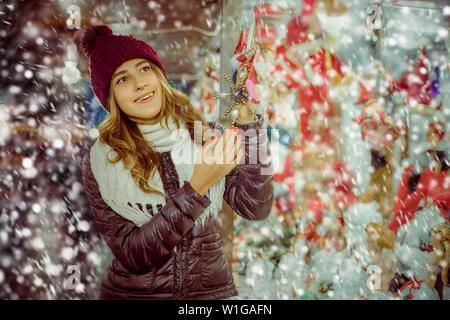 Cheerful  girl shopping at festive fair before Xmas - Stock Image